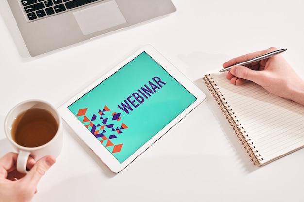 Выше вид неузнаваемого бизнес-менеджера, который сидит дома и делает записи во время бизнес-вебинара.