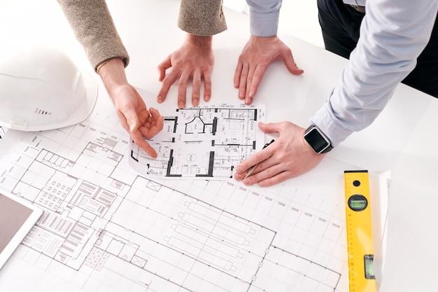 建築家と話し合いながらフラットプランを指している認識できない起業家のビューの上