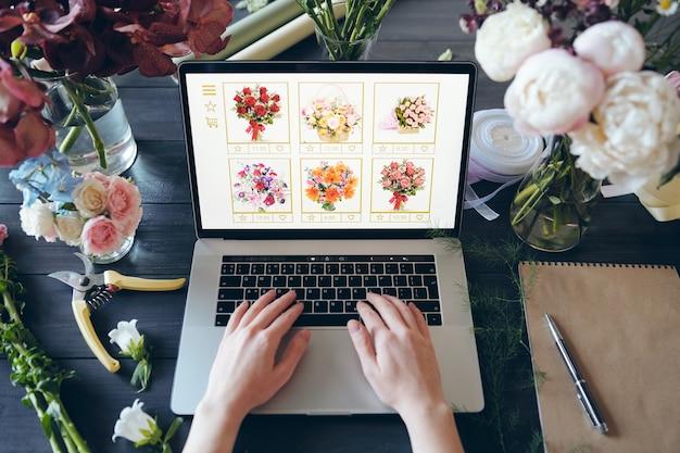 自分の店で花のオンライン注文をしているときに、美しい花と手用具が机に立ってラップトップのキーボードで入力している認識できない花屋のビューの上