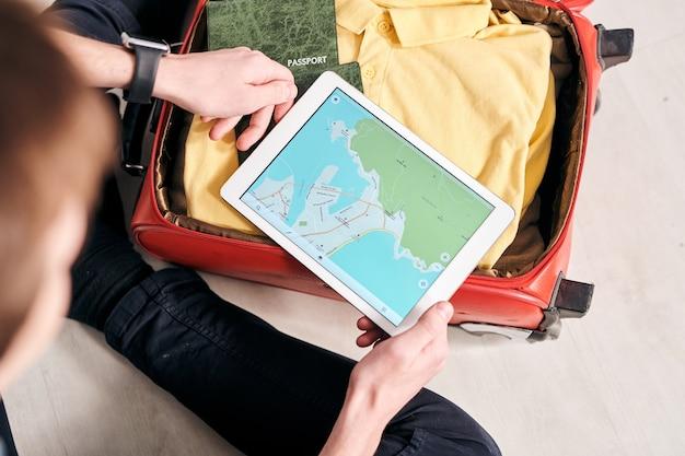外国での観光ルートを計画している間、スーツケースを梱包し、タブレットでオンライン地図を使用して認識できない男性のビューの上