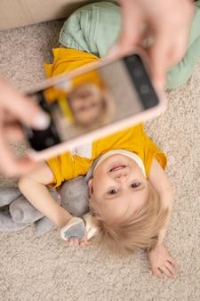 床におもちゃで横たわっている幸せなかわいい息子の写真を撮っている間スマートフォンを使用して認識できない親のビューの上
