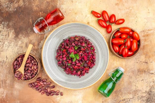 混合色の背景にスプーンで落ちたオイルボトルと茶色のポットの内側と外側にトマトと豆の酢のサラダのビューの上