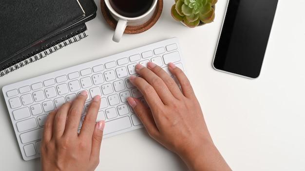 白いオフィスの机の上にキーボードで入力する女性の手のビューの上。