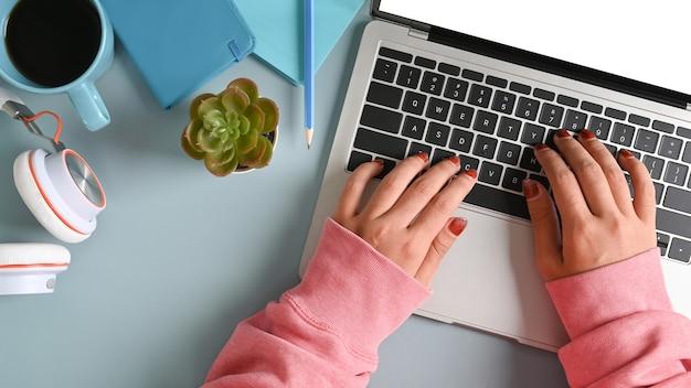 Выше мнение руки женщины печатая на портативном компьютере на ее офисном столе.