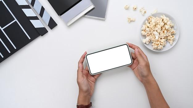 Выше вид женщины, держащей смартфон возле миски попкорна на белом столе.