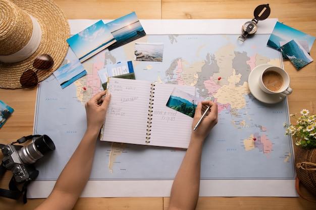 世界地図とテーブルに座って、観光スポットについてメモをとっている女性のビューの上