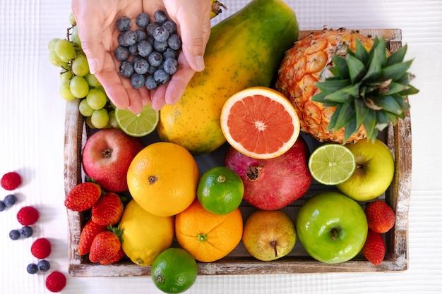 新鮮な色とりどりの果物でいっぱいの木製バスケットのビューの上。ブルーベリーのグループを保持している成熟した女性の手。健康的な食事とライフスタイル。白色の背景