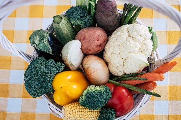 さまざまな新鮮な生野菜の健康的な食事とキッチンの木製バスケットの上のビュー