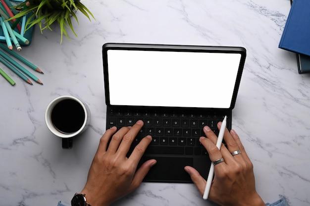 スタイラスペンを保持し、大理石のテーブルでデジタルタブレットで作業している若い男のグラフィックデザイナーのビューの上。