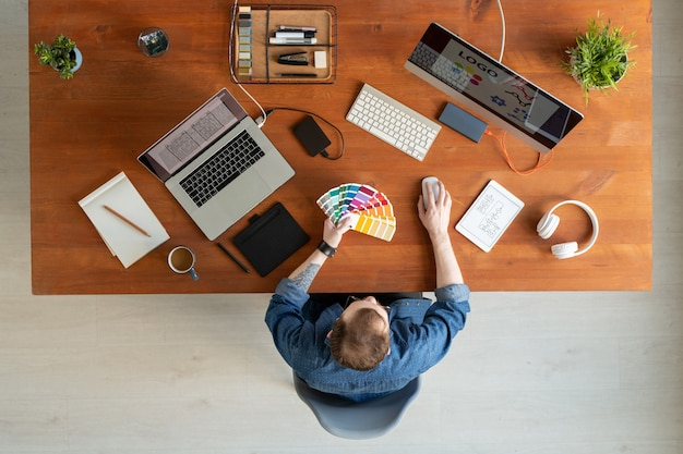 Выше вид молодого человека в джинсовой рубашке, выбирающего цвет на образце во время работы над фирменным стилем компании.