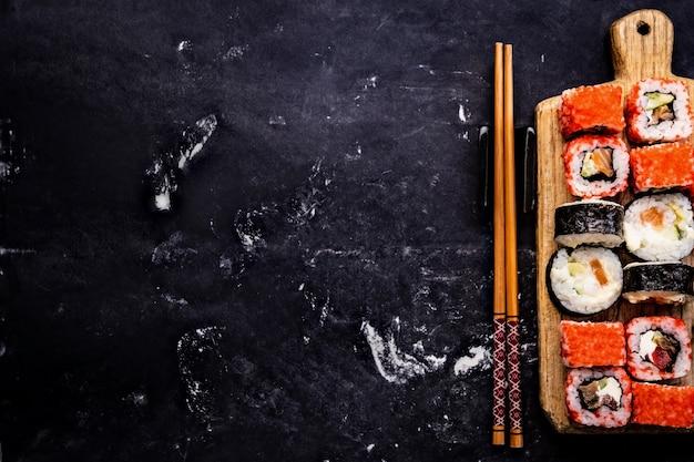 Вид сверху на набор суши-маки, подаваемый на деревянном планшете с палочками для еды, японские азиатские роллы, пищевые композиции ...