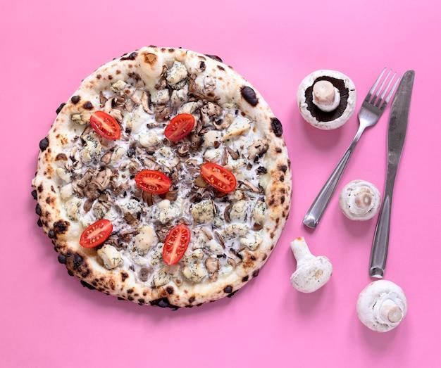 Выше вид пиццы на розовом фоне