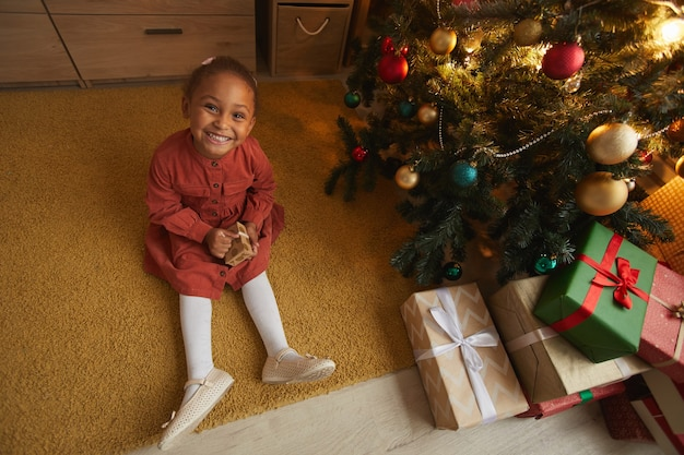 Выше вид портрет возбужденной афро-американской девушки, открывающей рождественские подарки, сидя у дерева дома и улыбаясь в камеру, скопируйте пространство