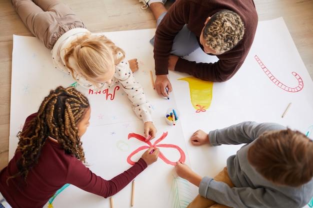 Выше вид портрет учителя-женщины, сидящей на полу с многонациональной группой детей, рисующих картинки, наслаждаясь уроком искусства, копией пространства