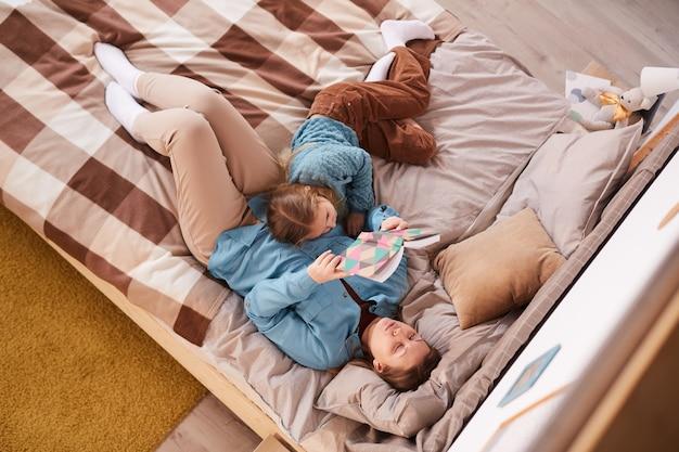 Выше вид портрет матери, читающей книгу, лежа на кровати со спящей дочерью дома, копия пространства