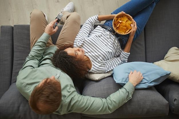 自宅でテレビを見たり、快適なソファに横になって軽食を食べている若い混血カップルのビューの肖像画の上
