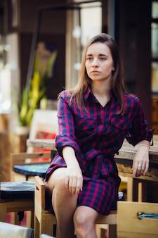Над взглядом милая женщина в фиолетовом клетчатом платье сидя на таблице на террасе в столовой.