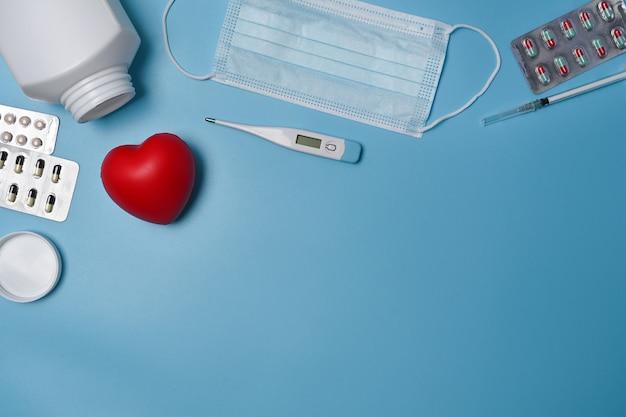 上図保護マスク、赤いハート、温度計、青い背景の薬の丸薬。
