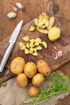 Выше мнению сырой картофель на деревянной доске