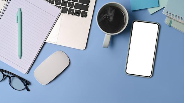 Выше вид смарт-телефон, кофейную чашку и блокнот на синем фоне.