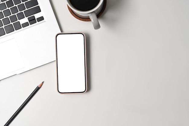 Выше вид смарт-телефон, ноутбук портативный компьютер на белом офисном столе.
