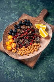 Вид сверху вкусные кусочки мяса, жареная еда с фруктами внутри тарелки на темно-синем фоне