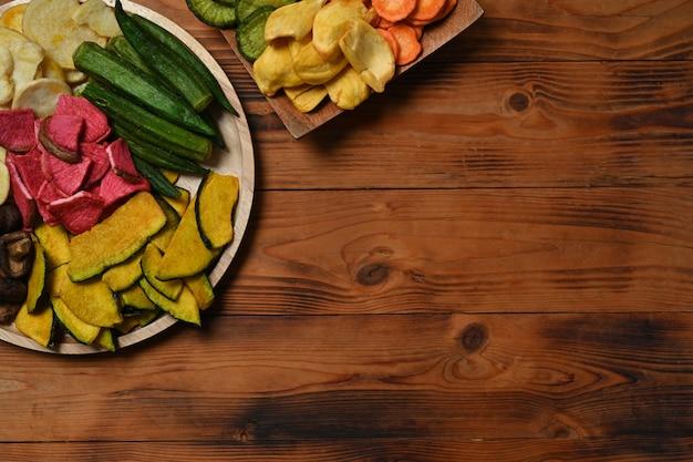 上の図は、木製の背景にオクラ、ニンジン、カボチャ、ビートルート、椎茸の野菜チップスです。