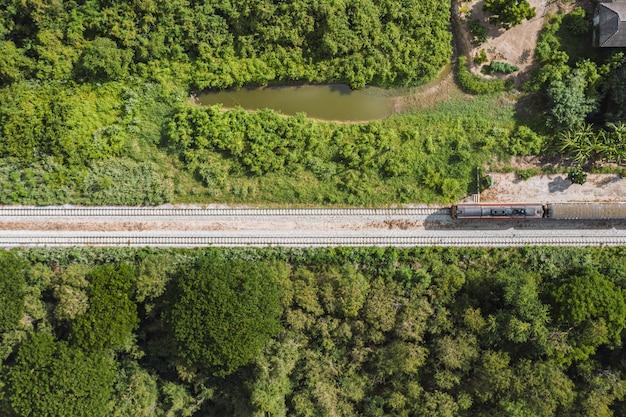 Выше, старинный поезд, едущий по железнодорожным путям в тропическом лесу в сельской местности