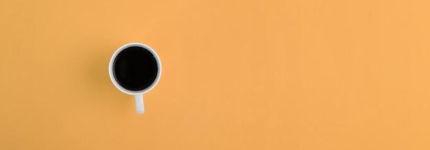 Выше вид белая чашка с кофе на оранжевом фоне с копией пространства.