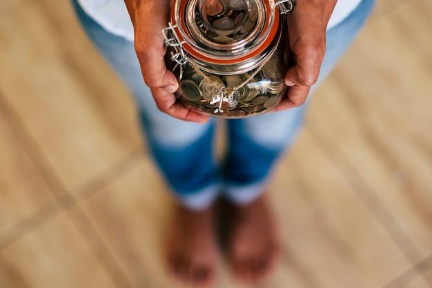 焦点がぼけた上図。次の旅行や休日の夏休みのためのお金を節約するガラスの透明な貯金箱の概念