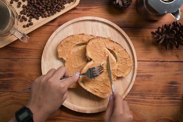 上の図の女性は木製のテーブルでピーナッツバターとトーストパンを食べています。