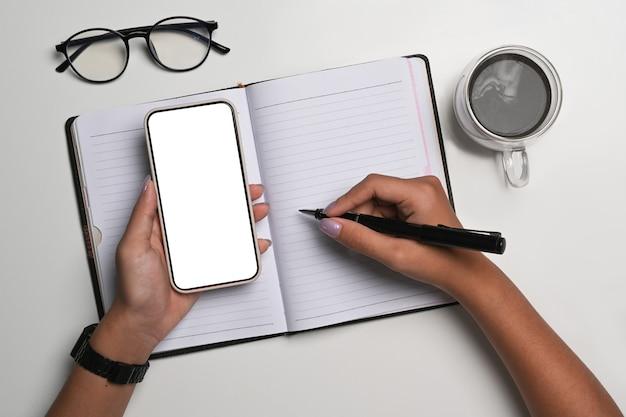 Выше вид женщина, держащая смартфон и писать на ноутбуке.