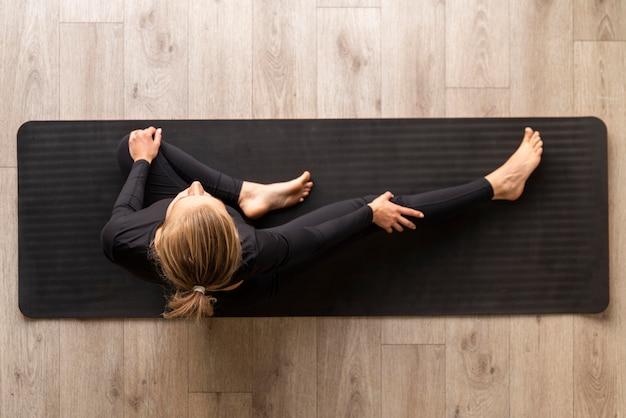 Выше вид женщина, практикующая йогу