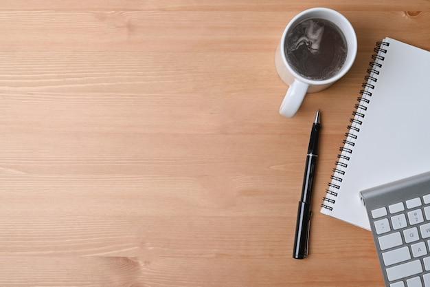 Выше вид деревянный офисный стол с чашкой кофе, ноутбуком и клавиатурой.
