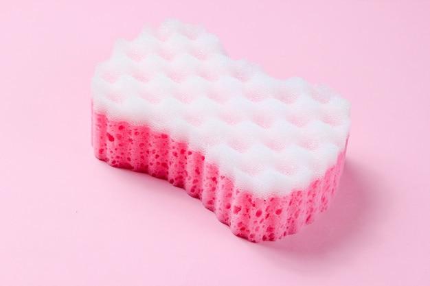 Abrasive double-sided sponge on a pink pastel background.