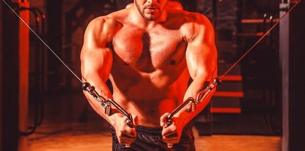 腹筋と上腕二頭筋。フィットネスマンはジムでエクササイズマシンケーブルクロスオーバーでエクササイズを実行します。ジムで大きな筋肉を持つハンサムな男。ジムのマシン