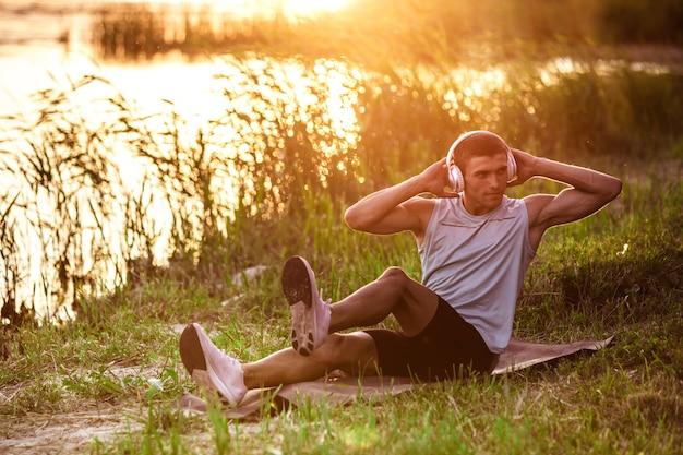 Abs 크런치. 운동하는 젊은 운동 남자, 야외 강변에서 음악을 들으며 훈련.