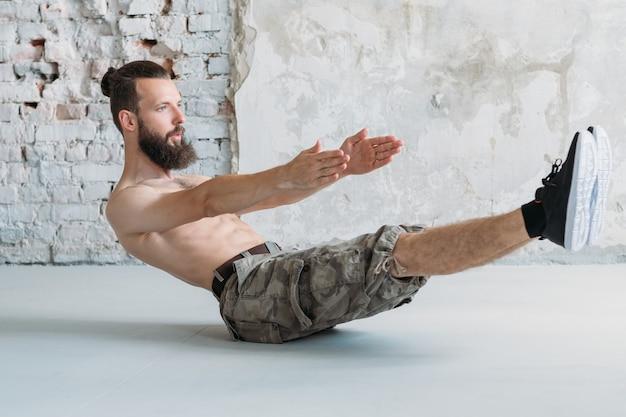 腹筋トレーニングと持久力運動。腹筋ホールドをしている男。ヨガやピラティスのコンセプト。