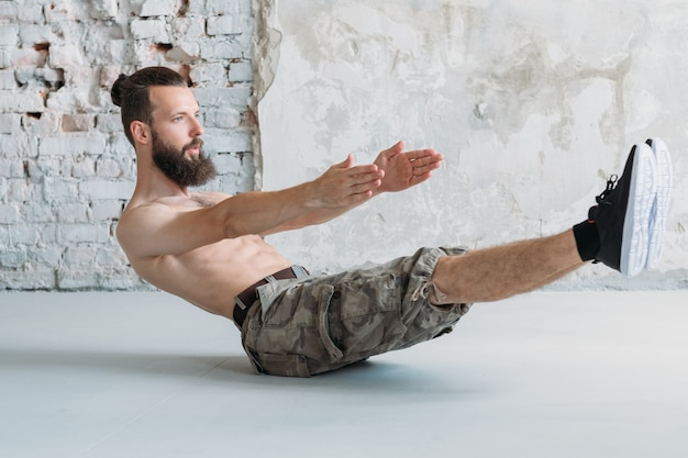 Abs training and endurance exercises. man doing abdominal muscle hold. yoga or pilates concept.