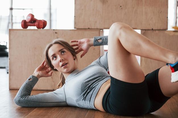 Качать пресс. спортивная молодая женщина имеет фитнес-день в тренажерном зале в утреннее время