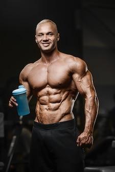 ジムの裸の胴体フィットネスコンセプトでトレーニングクロスフィットネスとボディービルのコンセプトジムabs筋肉運動後のスポーツ筋肉フィットネス男飲料水