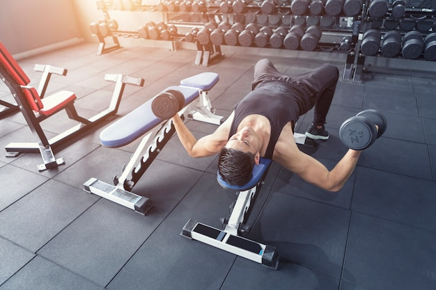 Молодой человек делая тренировку для мышц abs в спортзале.