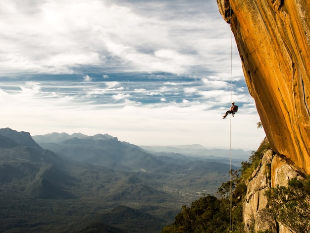 Abseiling a negative yellow rock wall with mountains