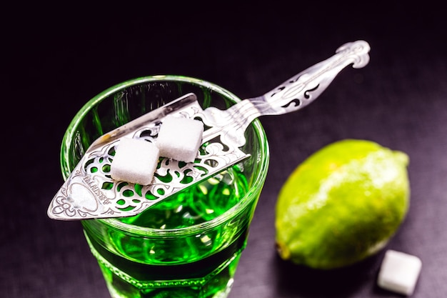 Absinthe in glass with lemon slices on dark surface with white sugar