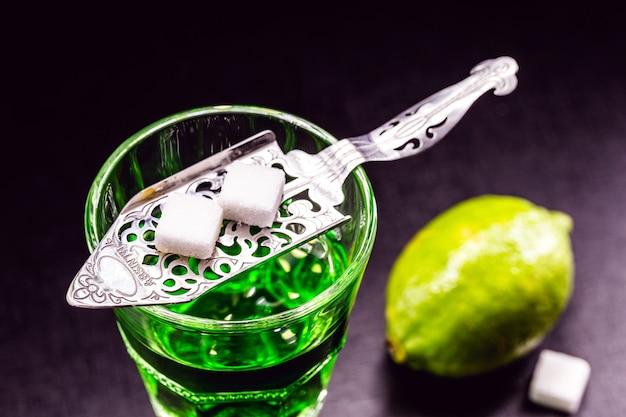白砂糖と暗い表面にレモンスライスとガラスのアブサン