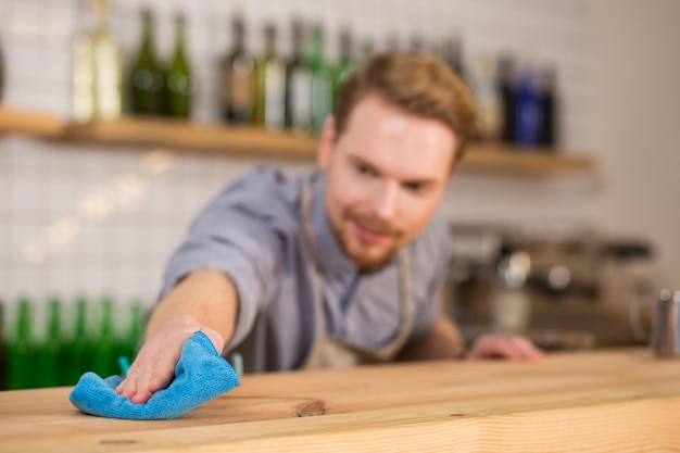 Absolute cleanness. selective focus of a blue duster being used for cleaning the surface of the table