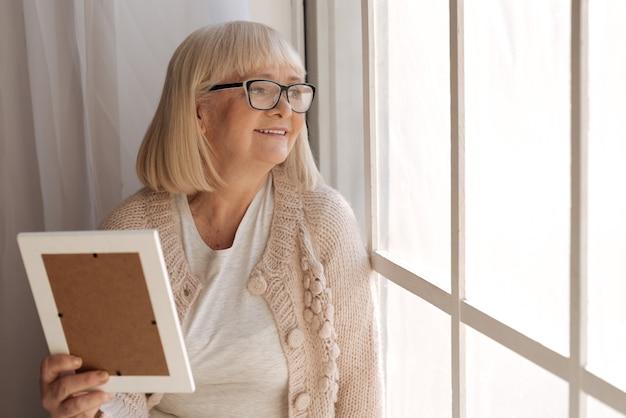 絶対に幸せです。素敵な気分で笑顔で窓を覗き込んでいる嬉しい陽気な白髪の女性