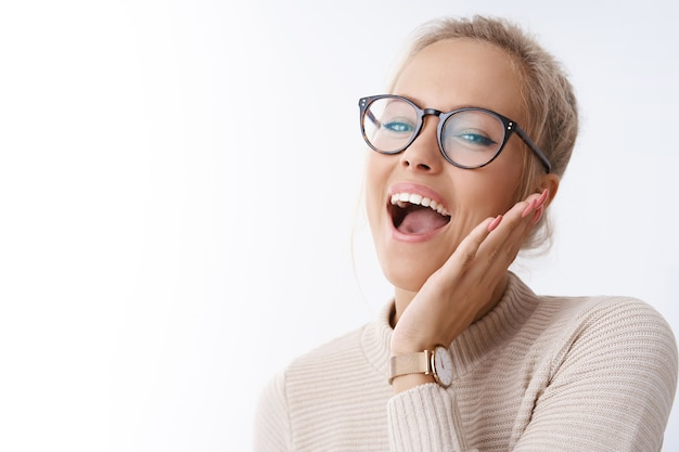 Absolutely happy. studio shot of amused and excited carefree joyful woman relaxing having fun singing and smiling cheerful touching cheek raising head dancing against white background happily