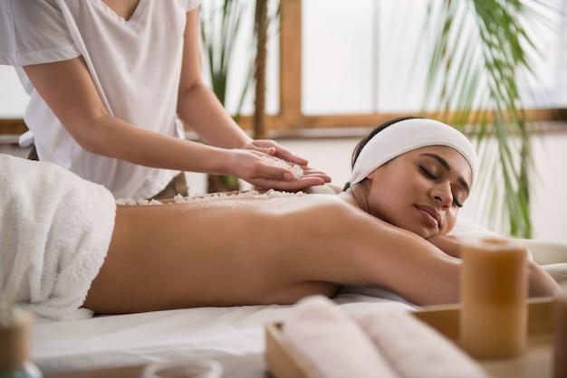 Абсолютно мирно. спокойная молодая женщина чувствует себя расслабленной, наслаждаясь массажем