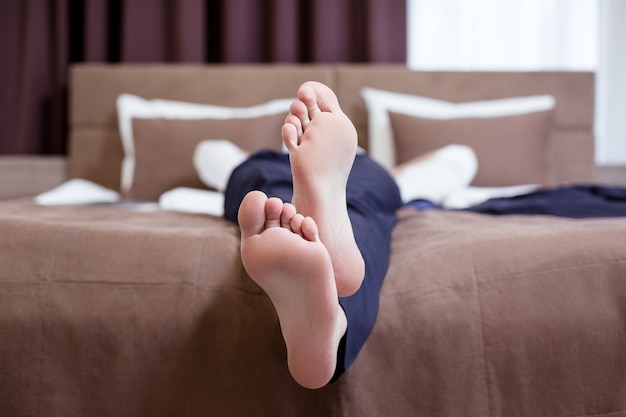 절대적으로 편안합니다. 침대에서 휴식을 취하는 동안 좋은 잘 생긴 사업가의 발 선택적 초점